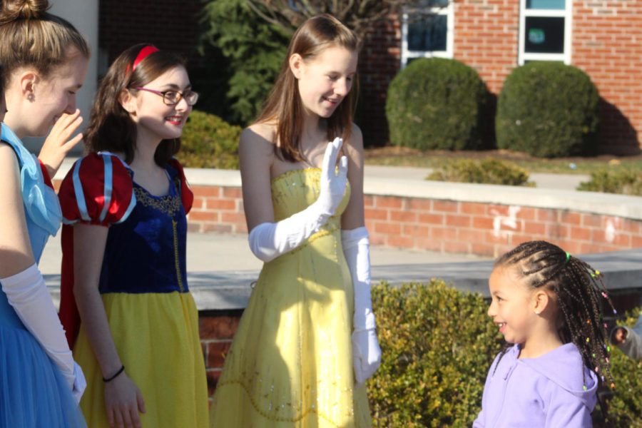 Juniors Carly Corso, Rachel Everard and Spencer Spears as Cinderella, Snow White, Belle say hello to an arriving elementary student.