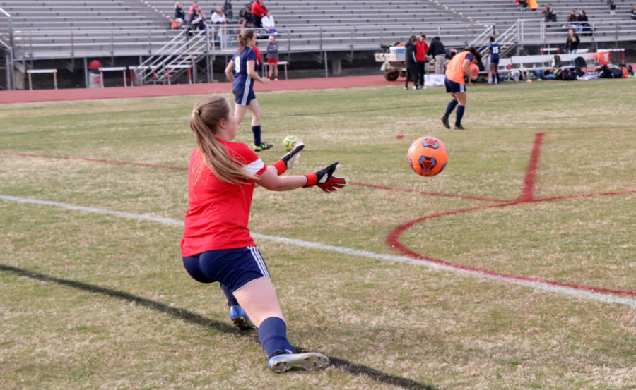 Eighth grader Carolyn Hinshaw leans to catch the ball during a shooting drill in warmups.