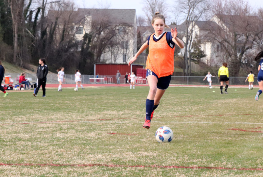 Eighth grader Jolie Sallah dribbles up the field to take a shot before the game starts.
