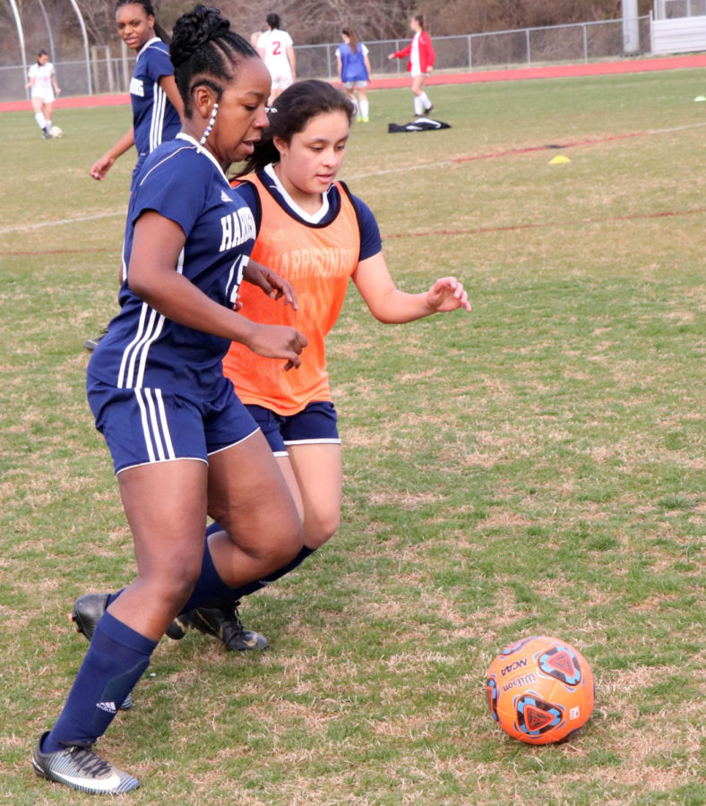 Eighth grader Zahria Ford and Santiago go after the ball during warmups.