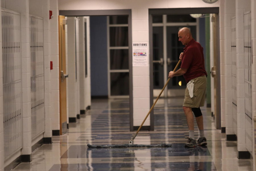 Janitor Carl Miller sweeps the hallways after school hours as part of his job as janitor.