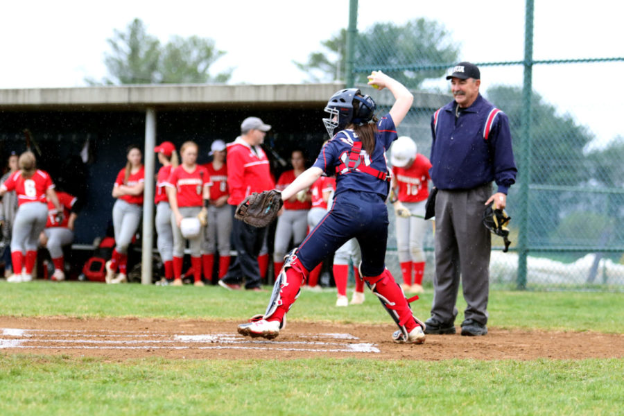 Junior catcher Lydia Grogg throws the ball back to the pitcher prior to the start of the inning.
