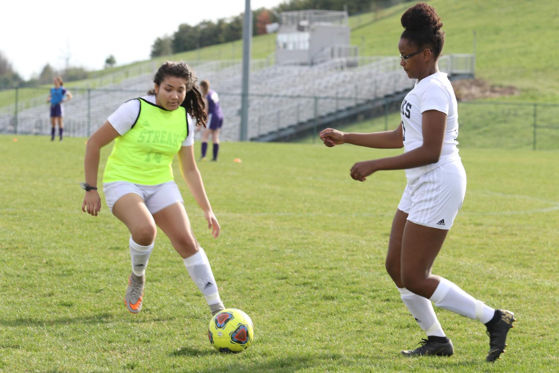 Sophomore+Esther+Manson+possesses+the+ball+during+warm+ups+against+freshman+Stephanie+Ramirez-Ruiz.