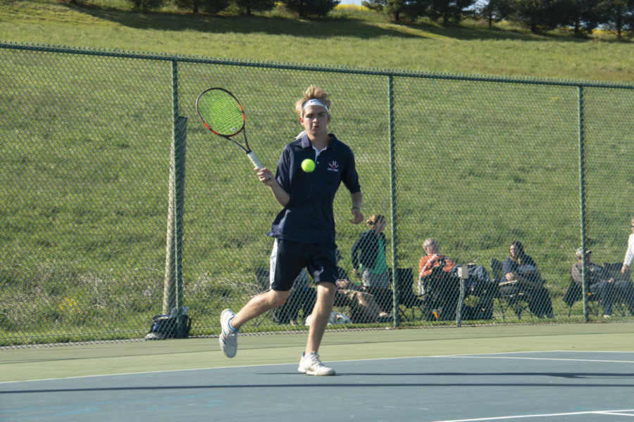 Senior John Collier approaches the net to hit a forehand.