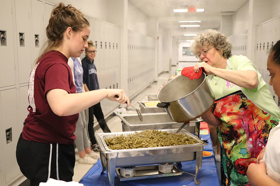 Karen Fansler-Ryan pours in the green beans while senior Audrey Knupp spreads them in the pan.