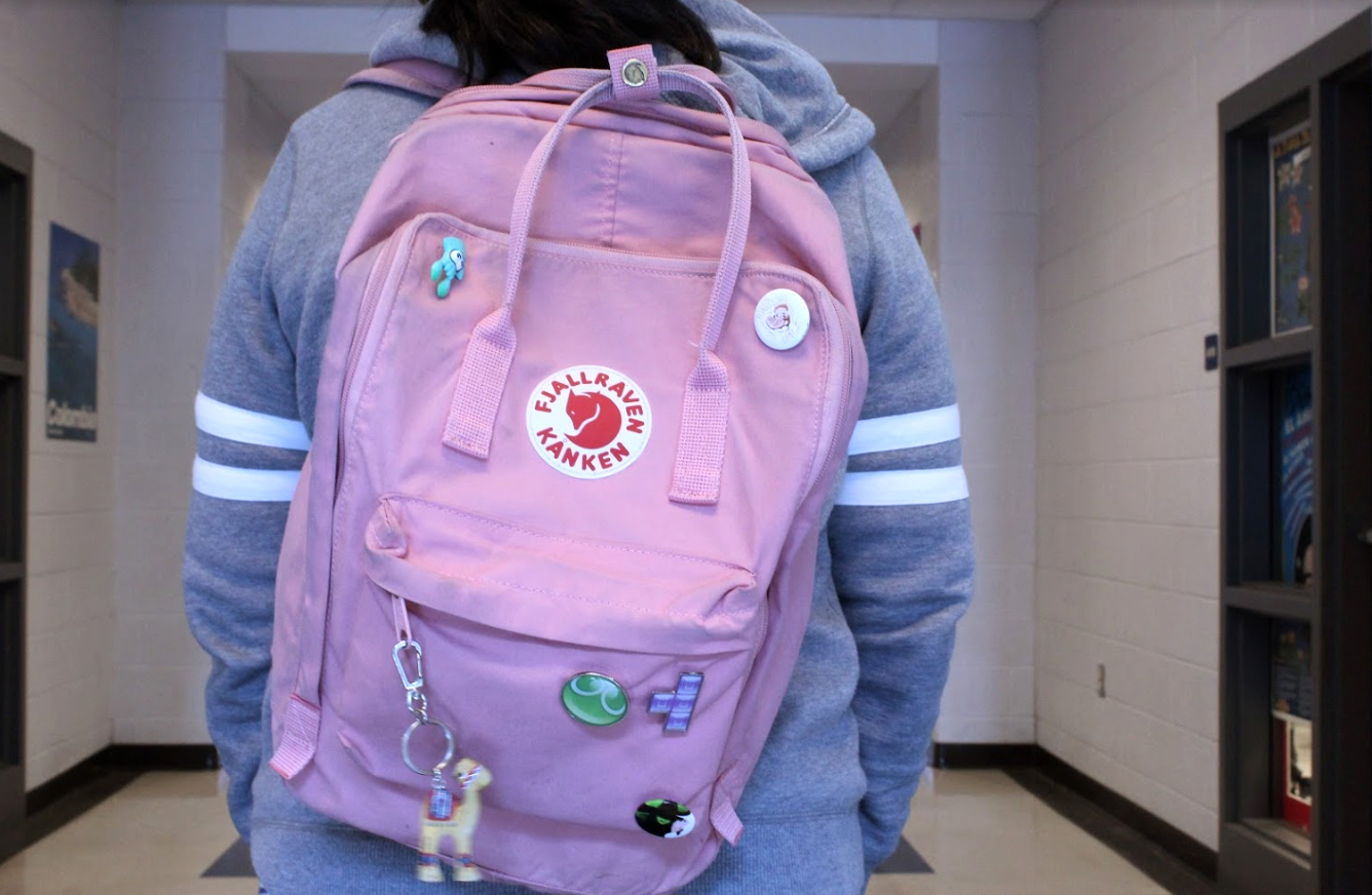 A student wears a light pink Fjallräven Kånken bag to school. Mattson believes that their high price and small size make them inconvenient.