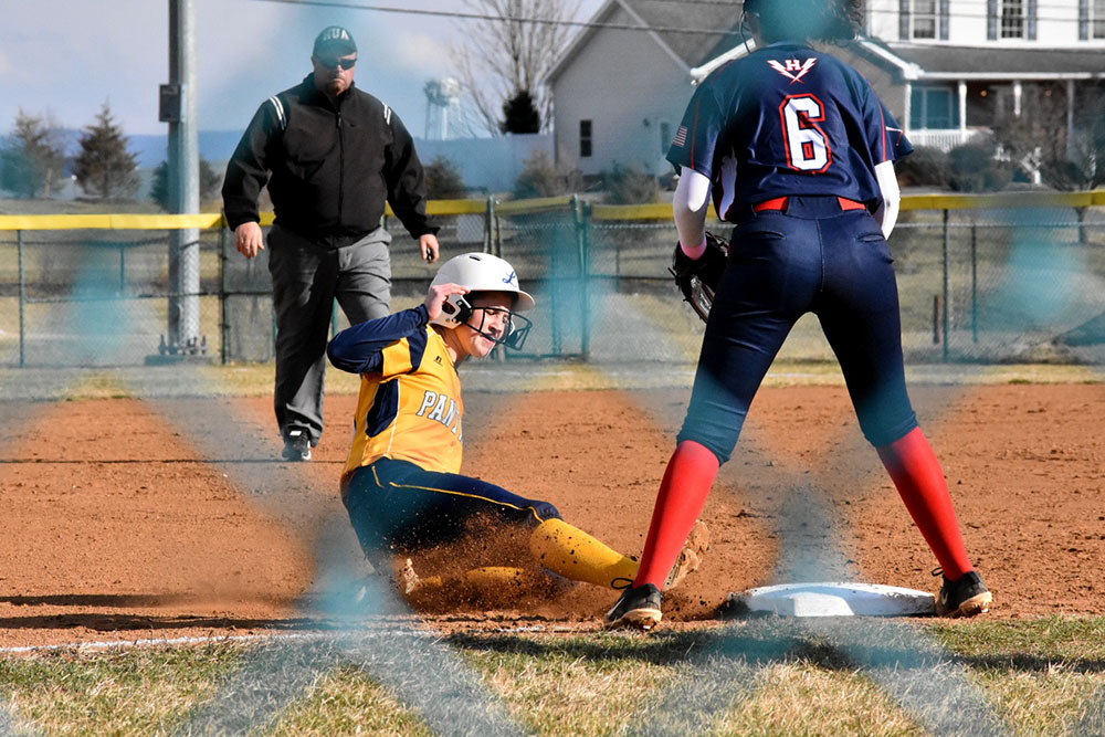 Sophomore+Alyssa+Sutton+awaits+the+ball+as+an+opposing+player+slides+towards+the+plate.