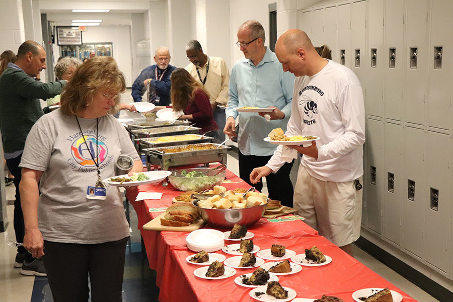 ASL teacher Julie Foster looks at her many choices of dessert before choosing one.
