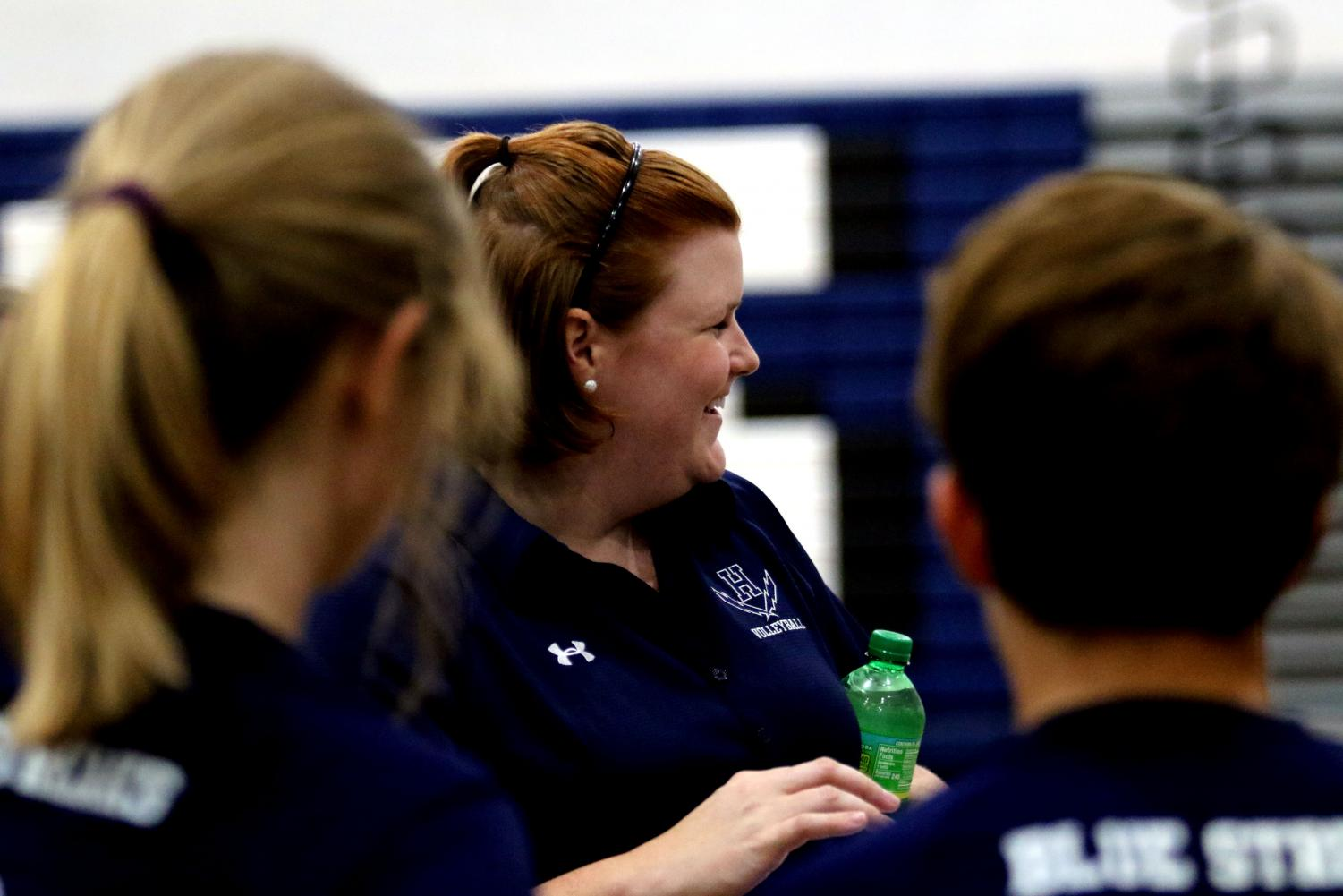 JV+coach+Danae+Delozier+shares+a+laugh+with+her+team+during+warm+ups+before+their+match+against+Rappahannock+High+School.+