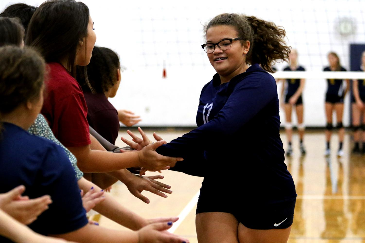 Freshman+Aurora+Lindstrom+gives+high+fives+to+the+varsity+team+prior+to+the+start+of+the+JV+volleyball+game.+
