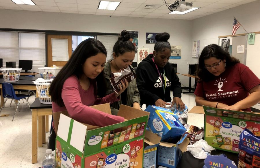 (From left) junior Helen Rivera Rivas, sophomore Marelyn Rivera Rivas and seniors Nayelis Pluma-Ferrer and Estefani Rivas-Sierra unpack food items to put in care packages for area first responders. This project was HOSA's first of the year in honor of 9/11.