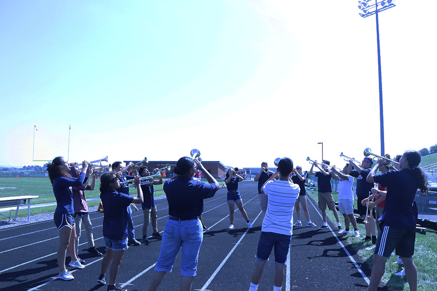 HHS+trumpets+perfect+their+music+before+their+performance+at+the+football+game.