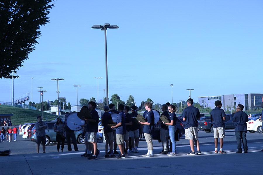 Blue+Streak+drum-line+marches+across+the+sidewalk.