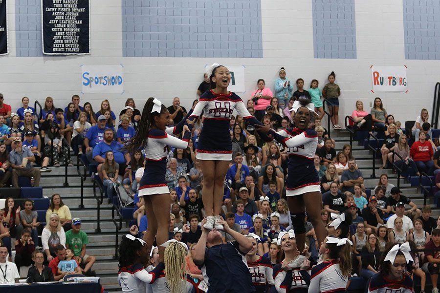 Junior Ruby Arndt does a one man stunt while juniors Nissi Gotay and Dorothy Yates support her.