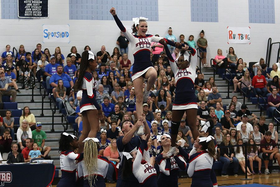 Junior Lizzy Healy completes a lib stunt while junior Dorothy Yates supports her arm.