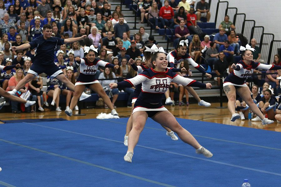 Junior Chloe Nichols and other members of the competition cheer team do a toe touch jump.