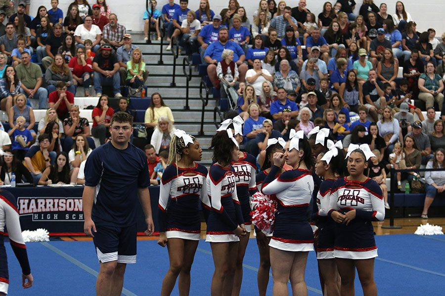 The competition cheer team meets in the middle of the mats after stopping their routine due to senior Lydia Grogg sustaining an injury.