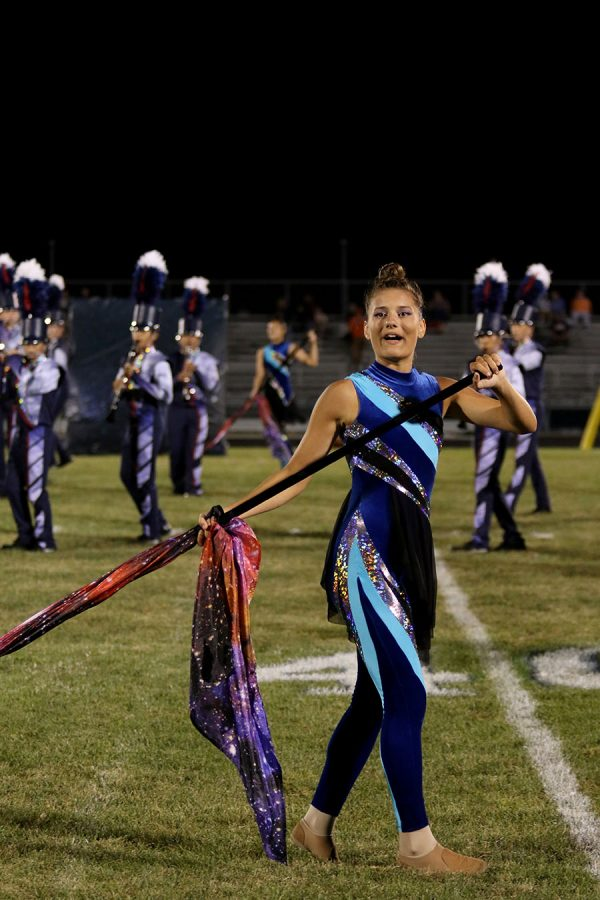 Senior colorguard member Alexa Coburn shows off her new outfit and galaxy flag in the theme of