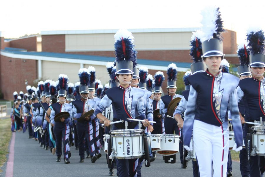 The HHS marching band marches towards the football field after the tailgate at the home football game Sept. 20, 2019.