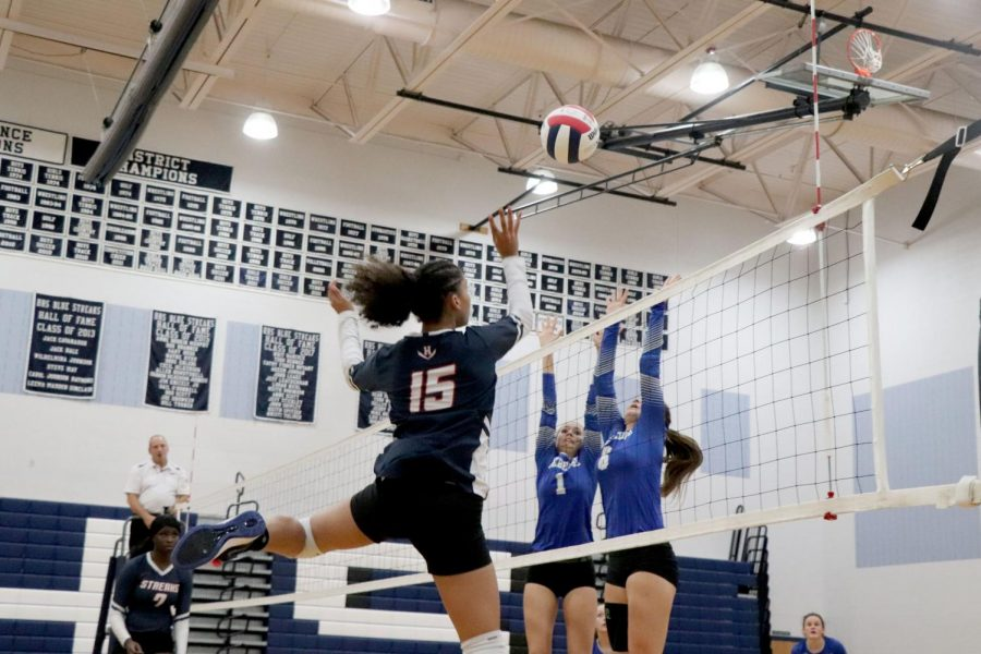 Sophomore Jay Garcia hits the ball above a block.