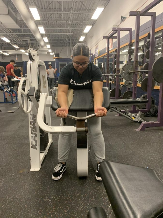 Diaz uses the arm curl machine to train during her weightlifting class.