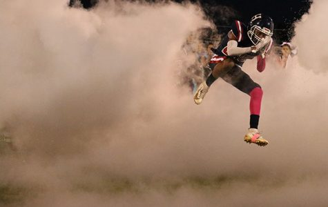 Junior #25 Marquez Sly jumps through the wall of smoke while entering the field before the game.