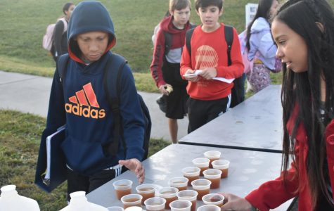 Students grab a small cup of apple cider from the table stationed outside of the track.