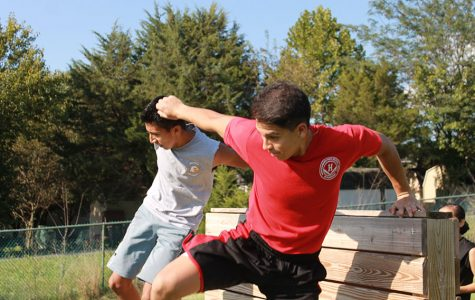 Cadet Major junior Jeremias Domingo and C captain sophomore Guillermo Lopez jump off the wall of the team physical fitness course.