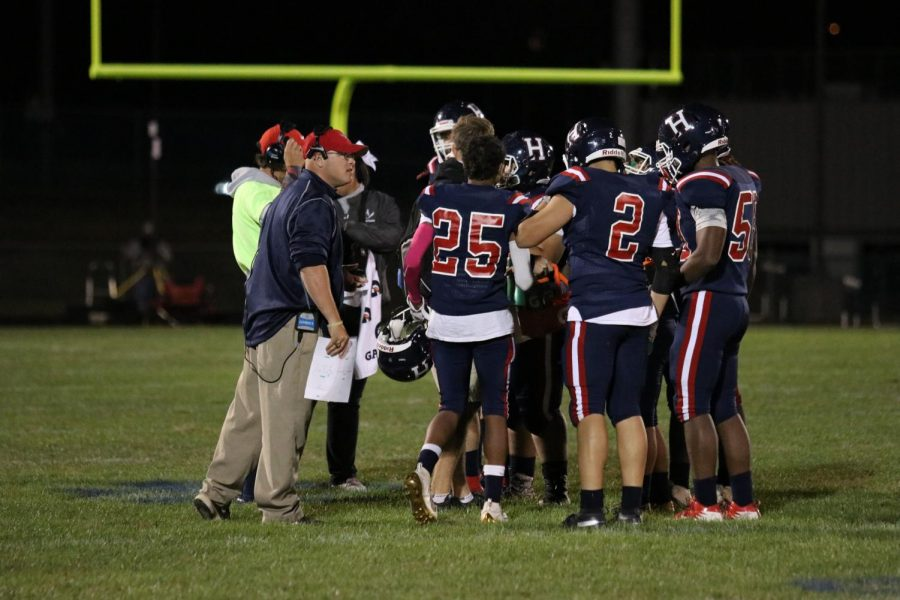 During a timeout, the defense huddles on the field to develop their second quarter game plan.