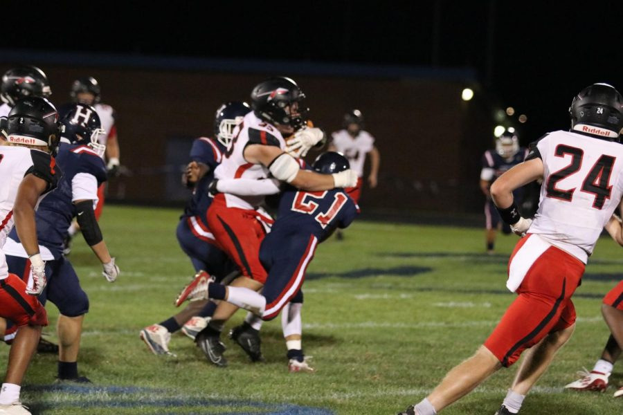 As Sherando progresses down the field, sophomore defensive back, Guillermo Lopez Mejia (#21), makes a tackle to stop the ball.