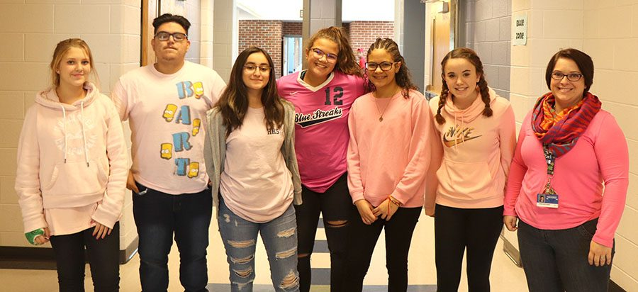 A group of freshmen and juniors pose along with their teacher for pink out day.