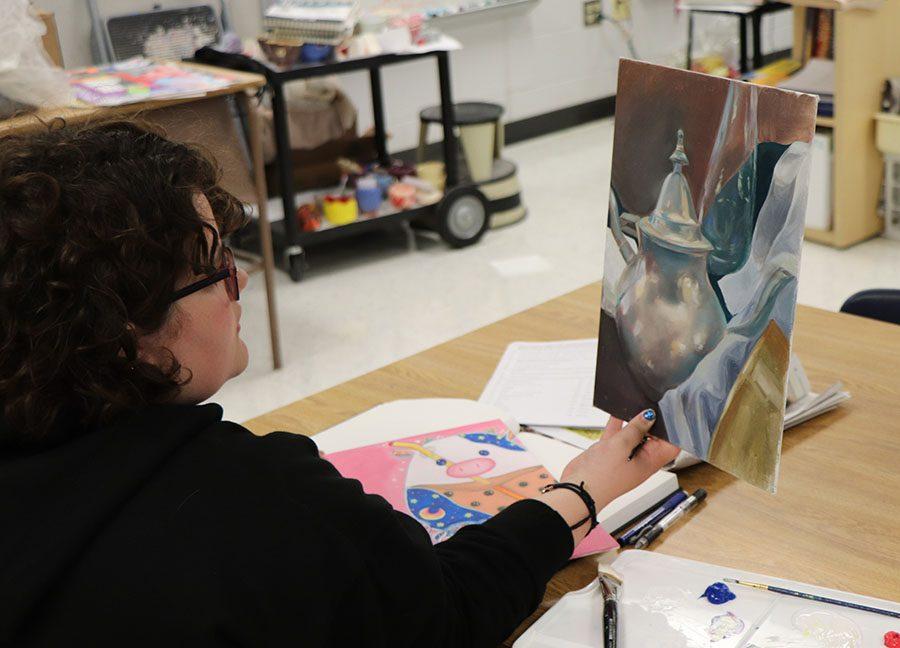 Junior Maggie Botticelli  admires, sophomore, Julia Whites piece of art.