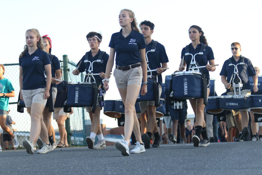 Seniors and band leaders Alice McNett and Claudia Obenschain lead the marching band to the football field during a home football game.