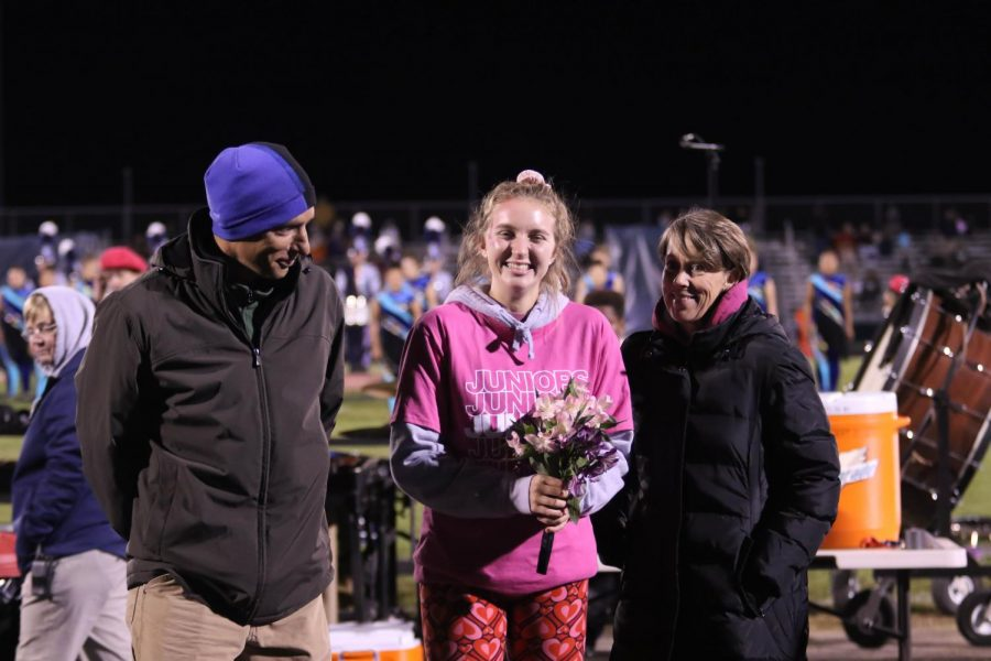 Junior Sophie Sallah and her parents walk out at halftime.