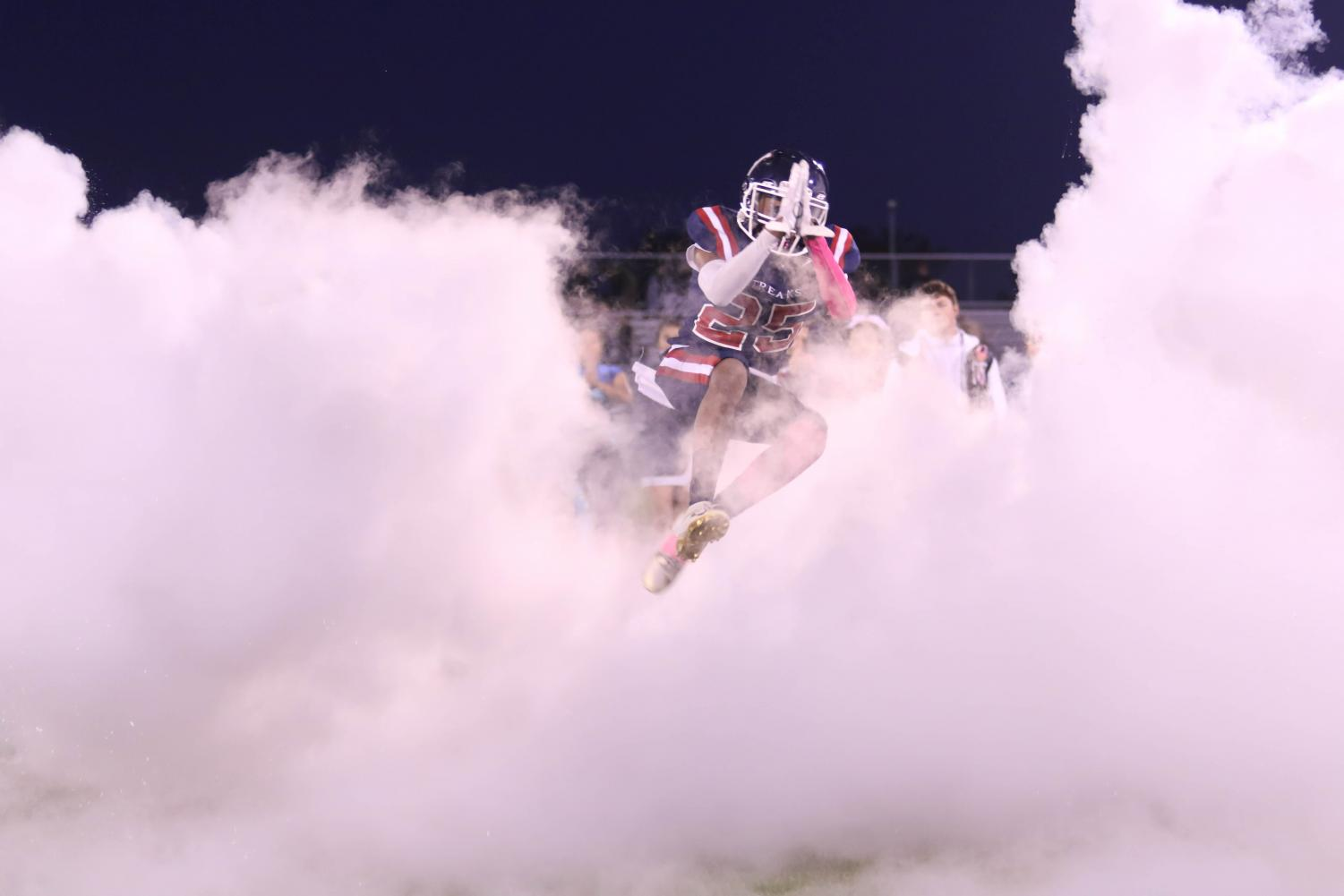 Junior Marquez Sly jumps through the smoke prior to the Streaks' home game versus Broadway.