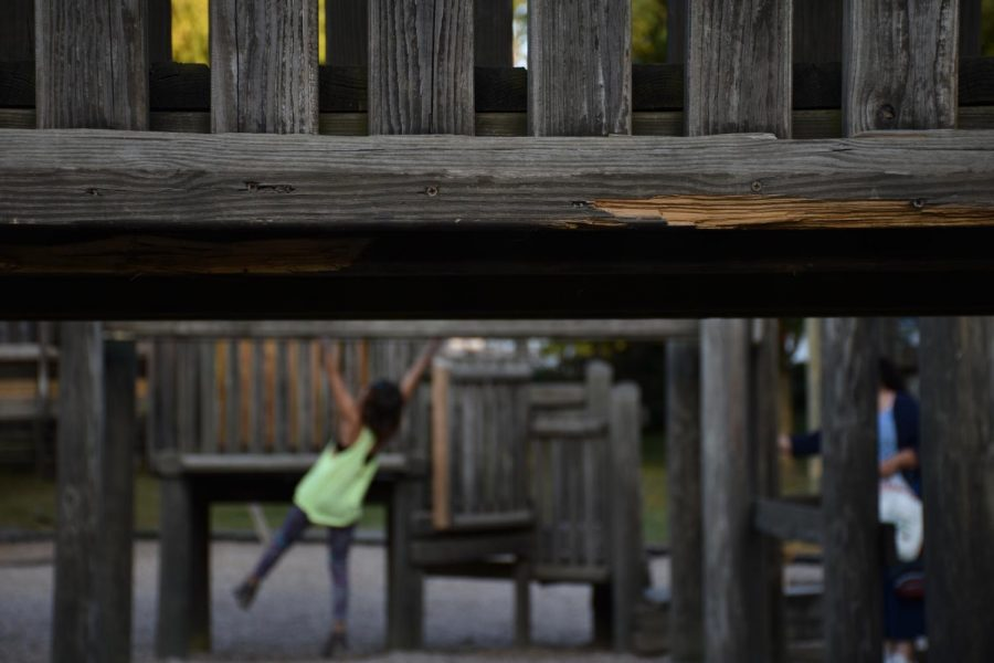 A+damaged+plank+of+wood+is+exposed+to+the+elements+as+kids+play+on+the+monkey+bars+in+the+background.+