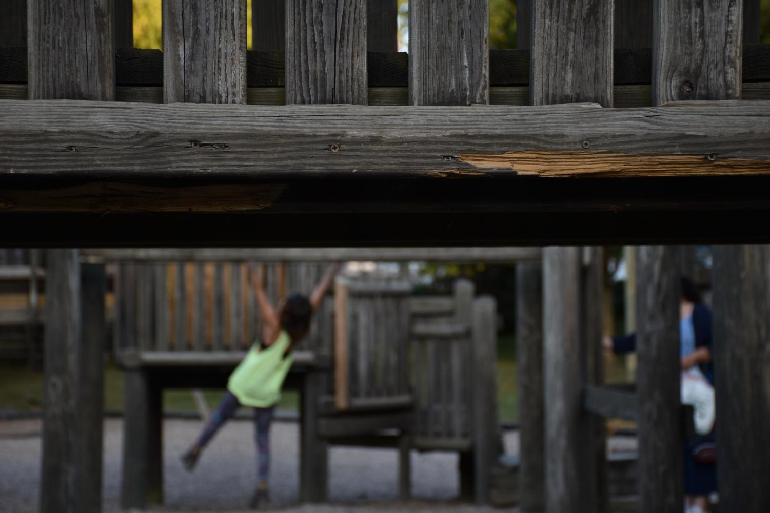 A damaged plank of wood is exposed to the elements as kids play on the monkey bars in the background.