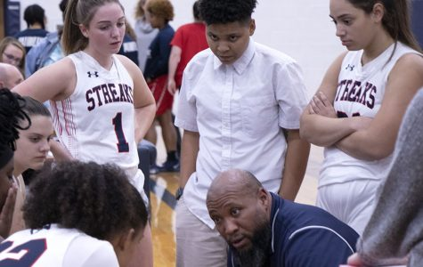 Coach Durmount Perry talks to  the girls basketball team during a timeout.