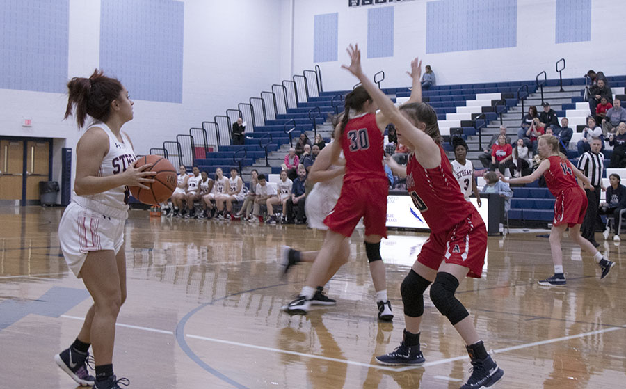 Sophomore Maria Tirado searches for a pass while being defended.