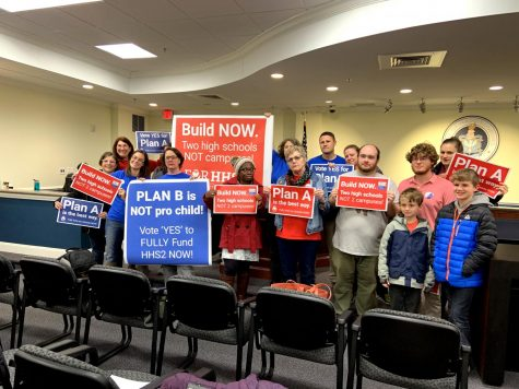 Community members who supported Plan A stand in City Council chambers following the vote to determine the plan for the new high school.
