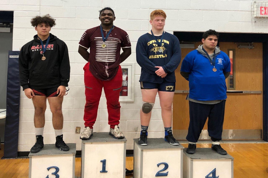 Junior Antwonne Washington stands on podium as the first place winner of a wrestling meet. Washington previously won at the Sophomore State Competition for wrestling as a sophomore.