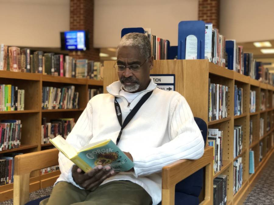 Mr.Martin+reads+a+book+at+the+end+of+a+bookshelf+in+the+library.+
