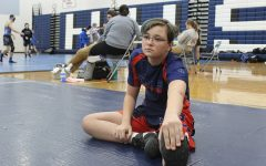 "Freshman Scott Lambert stretches before a wrestling match. Wrestling involves a lot of physical strain for Lambert. ""My favorite part is that even though you are competing individually, the team is one family,"" Lambert said. ""[The hardest part is] how much physical training it takes to wrestle."""