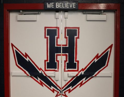 Varsity football coaches Joe Carico, Marc Healy and Josh Carico painted the inside of the weight room doors white with the Harrisonburg High School logo and painted the trim red.