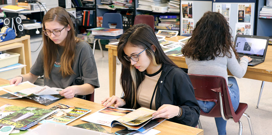 Sophomore Madison Horneber and junior Nicole Acusta look for pieces to go on their collage.