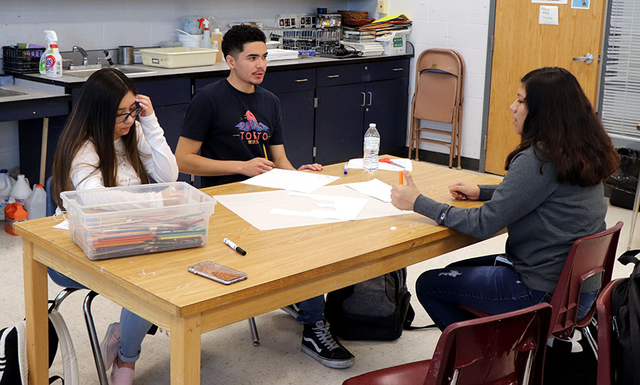 Senior Carlos Matute asks group members for help with his collage.