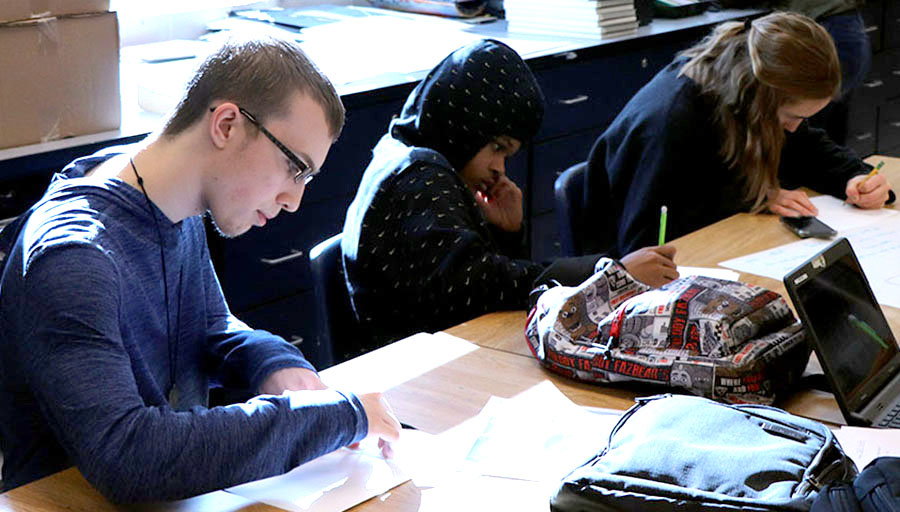 Sophomore Ethan Knicely works on a collage in his art class.