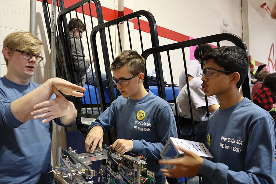 (Photo taken January 2020) Senior Thomas Shulgan and sophomore Niranjan Aradhey, members of team Error Code 404, regroup after losing a robotics match at a competition last year.