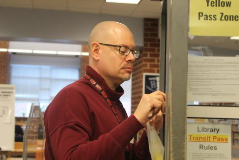 Library secretary Bradley Walton cleans up the tape on the door to the library.