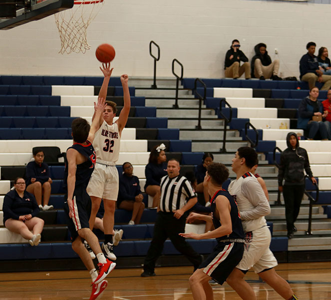 Sophomore+Evan+Bert+jumps+up+to+shoot+a+basket.
